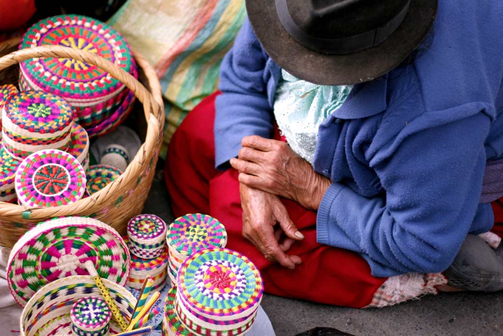 Indigenous woman sells handcrafted wicker boxes on an ecuadorian market